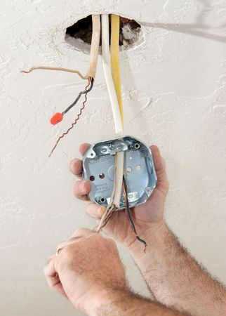 licensed: An electrician threading wire through a regulation fan ceiling box.  Work being performed to code by licensed master electrician. Stock Photo