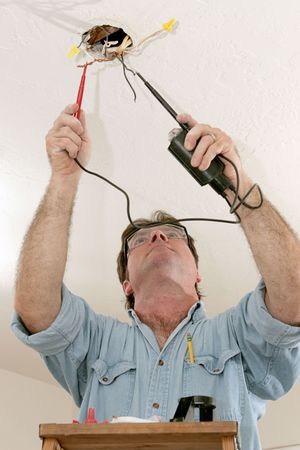 An electrician testing the voltage coming out of ceiling wires. Work is being performed to code by a licensed master electrician.