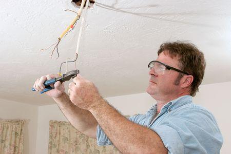 alicates: Un electricista utiliza alicates para enderezar y separar cables. El trabajo se est� realizando con el c�digo de licencia por un maestro electricista.