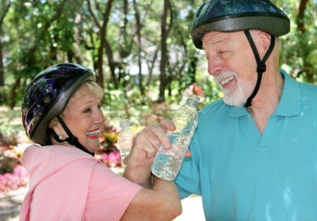 eachother: An attractive senior couple joking with eachother as they take a water break during a bike ride. Stock Photo