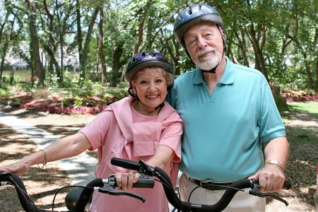 An attractive senior couple bicycling together wearing helmets. photo