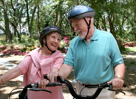 A happy senior couple staying fit by bicycling together.