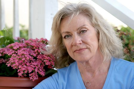 front porch: Una mujer envejecida media que mira en cuesti�n que se sienta en su p�rche de entrada.