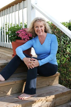 front porch: A beautiful, mature woman relaxing at home on her front porch.