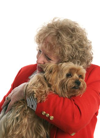 A woman giving her pet yorkie dog a big hug. Focus is on dogs face. photo
