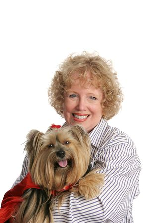 An adorable yorkie in a red cape and her happy owner.  Isolated. photo