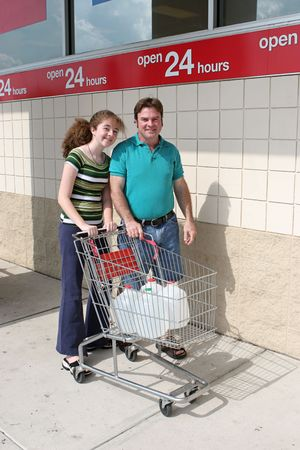 A father and daughter shopping for hurricane supplies.  Their cart is full of water jugs. photo