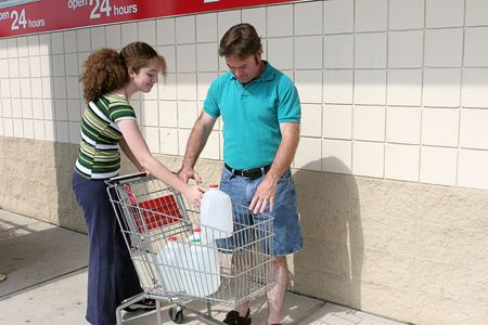 emergency cart: A father and daughter shopping for hurricane supplies.  Their cart is full of water jugs.  Image also appropriate for recycling.