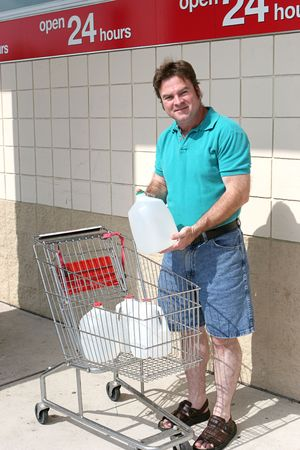 A man with a shopping cart full of water bottles in preparation for a hurricane.  Could also be used for recycling. photo