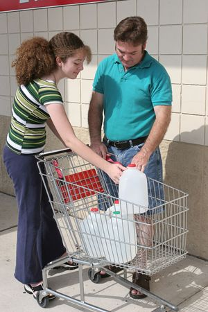 A father and daughter stocking up on hurricane supplies and filling their water jugs.  Also could be used for recycling. photo