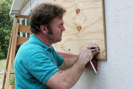 handy: A homeowner or handy man screwing plywood onto windows in preparation for a hurricane. Stock Photo