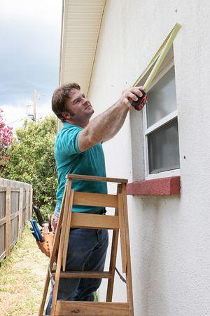 A carpenter or handyman measuring windows for storm shutters. Stockfoto
