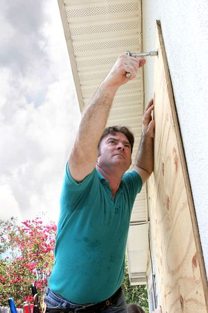 plywood: A homeowner covering his windows with plywood in preparation for a hurricane. Stock Photo
