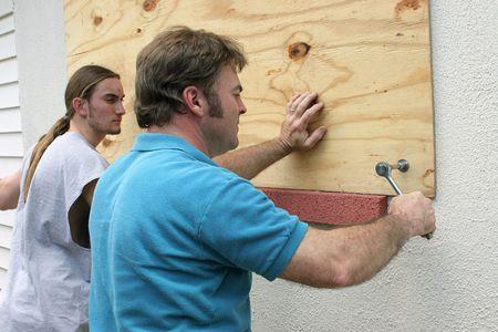 父 & 合板の上を置く窓、ハリケーンの準備の息子。 写真素材