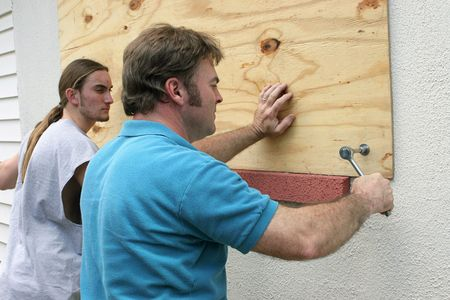 natural disaster: A father & son preparing for a hurricane by putting plywood over the windows. Stock Photo