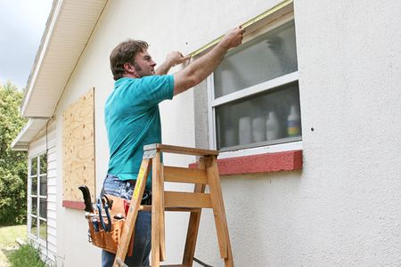 shutter: A man measuring windows for hurricane shutters or plywood. Stock Photo