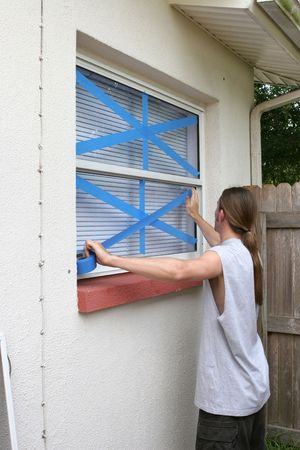 A teen using masking tape on his wondows to protect from broken glass during a hurricane.