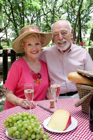 An attractive senior couple enjoying a picnic outdoors. photo