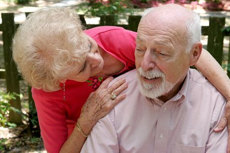 A senior couple.  The wife is caring for the husband. photo
