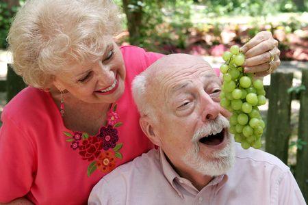 A senior couple joking around.  She is feeding him grapes. photo