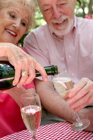 A senior couple - the wife is pouring champagne for the husband.  (focus is on bottle neck & champagne in glass) photo