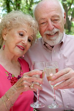 A beautiful senior couple toasting their years together with champagne.
