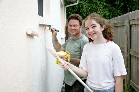 homeownership: A father and daughter painting the house together and having fun. Stock Photo