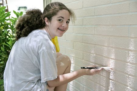 A cute teen girl helping out by painting the trim on her house. photo