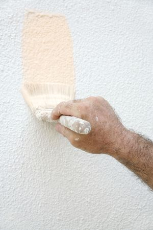 hairy arms: A mans paint-spattered hand holding a paintbrush and painting a house.
