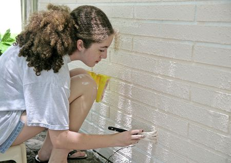 room for text: A teen girl painting house trim.  Room for text.