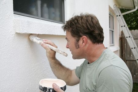 edging: A painter edging around an exterior window with a brush. Stock Photo