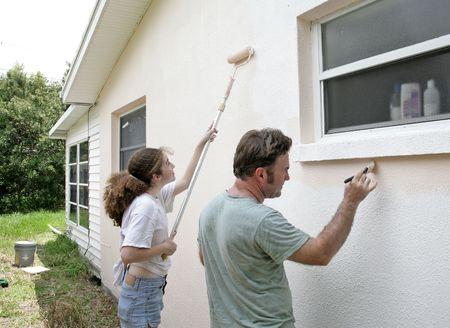 父と娘が一緒に彼らの家を塗るします。