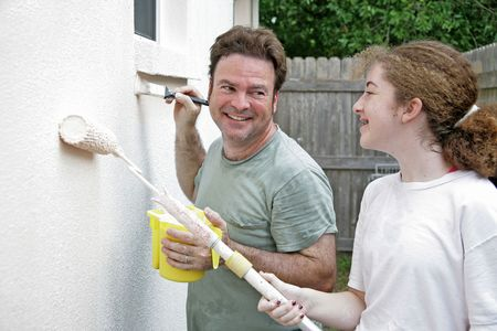 homeownership: A father and daughter laughing and smiling as they paint the house together. Stock Photo