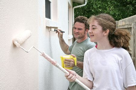 homeownership: A horizontal view of a father and daughter painting their house together.