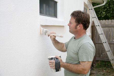 stucco facade: Una casa pittore, bordo attorno a una finestra con un pennello. Camera per il testo.
