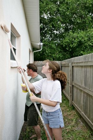 homeownership: A father and daughter painting the house togehter.  Vertical view. Stock Photo