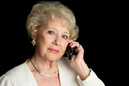 wealthy lifestyle: A beautiful senior lady talking on the phone with a serious expression.