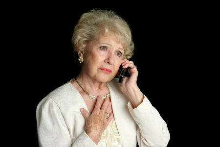 old cell phone: An elegant senior woman hearing sad news over the phone. Stock Photo