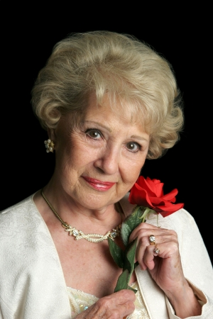 A portrait of a beautiful senior lady holding a rose. photo