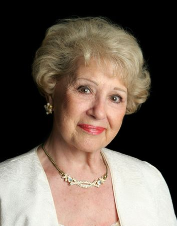 A beautiful senior woman, smiling and happy and dressed up in formal clothes. photo