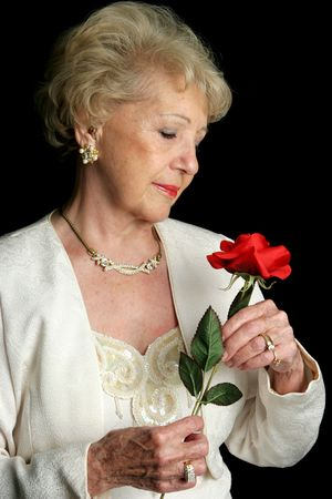 A beautiful senior lady holding a rose.  She is wearing a hearing aid. photo