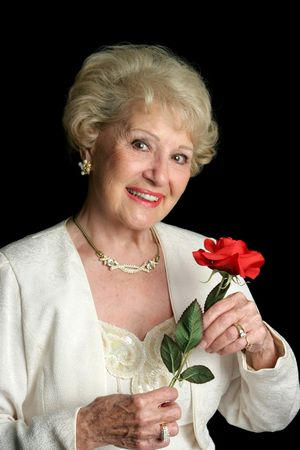 formal attire: A beautiful, successful senior lady dressed in formalwear holding a red rose. She has perfect teeth.
