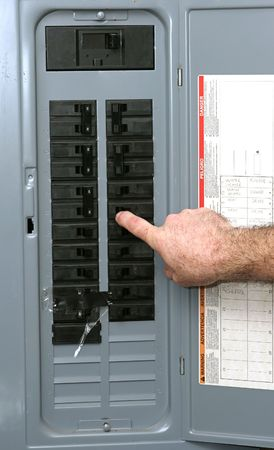 electrical panel: A closeup of an electrical panel with an electrician turning off the breaker so he can work safely according to OSHA standards.
