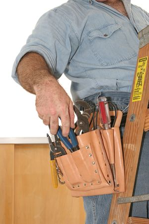 A closeup of an electricians tools in his tool pouch as he is working overhead on a ladder.
