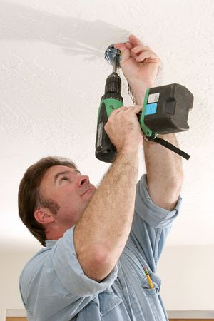 An electrician using a drill to install a fan box in the ceiling.  Work is being performed to NEC code standards by a licensed master electrician. photo