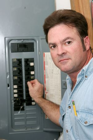 electrical panel: An electrician at an electrical panel turning off the breaker before commencing work.  Model is a master electrician and working according to NEC code and OSHA safety standards. Stock Photo