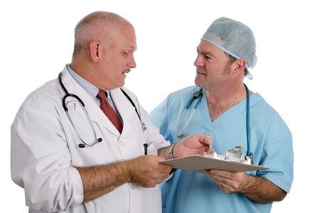 An older doctor instructs an intern as they discuss a patients medical history.  Isolated. photo
