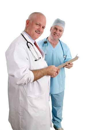 white coat: A vertical view of two friendly doctors reviewing a medical chart.  Isolated. (focus on doctor in white coat)