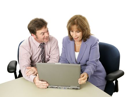 A male-female business team.  He is showing her something surprising on his laptop. Stock Photo - 513198