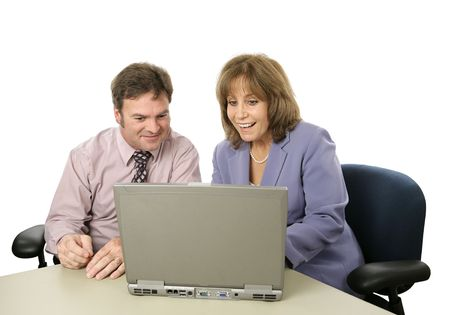 A male-female business team happy about what they see on the computer.  Isolated. 写真素材